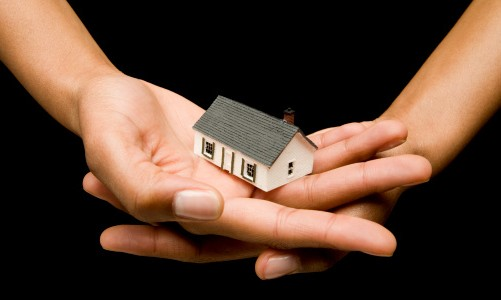 Human hands holding small house