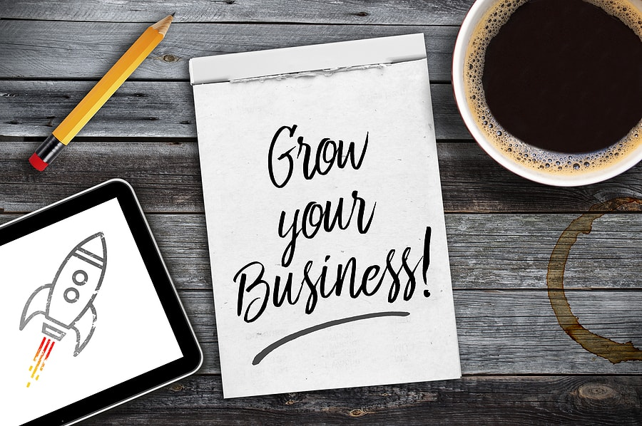 Sketchbook with written message Grow your business on a wooden desk with tablet, pencil and cup of coffee